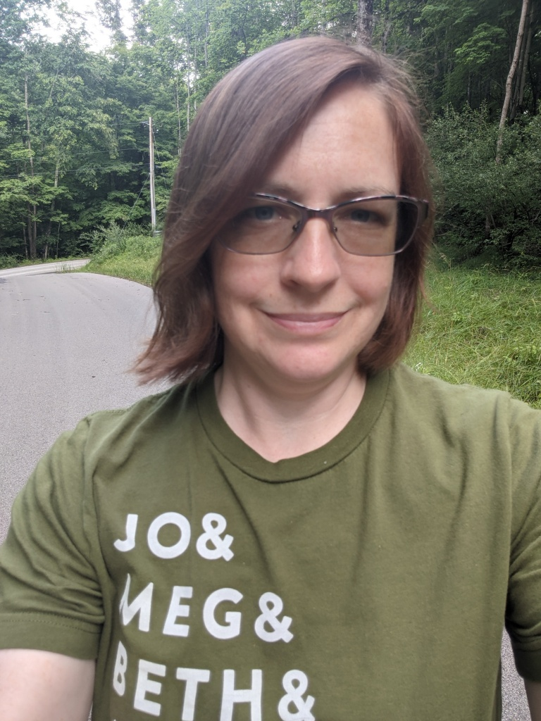 """An image of a woman with glasses and shoulder length brown hair smiles at the camera. She is wearing a green t-shirt with the words """"Jo & Meg & Beth & Amy & Marmee"""" written in white letters across the right side of the shirt."""